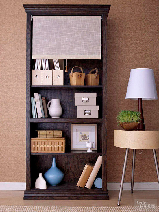 hidden storage ideas include a roll down shade for your bookshelf