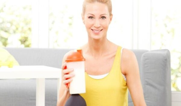woman sitting on the floor with weights holding a protein shake