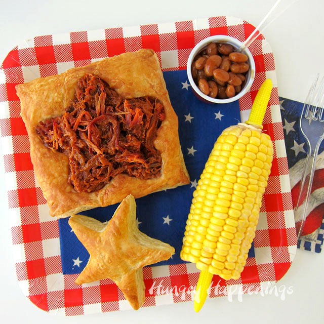 Puff pastry shaped in a star with bbq meat, corn on the cob and baked beans