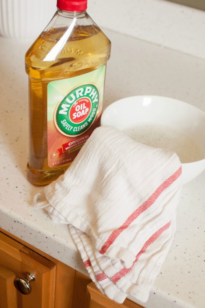 A bottle of Murphy's Oils Soap with a small bowl and cleaning rag.