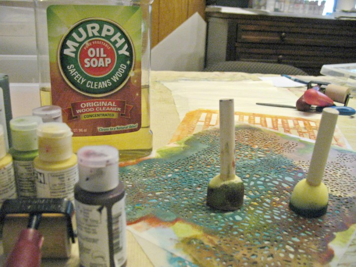 A bottle of Murphy's Oils Soap, bottles of paint, sponge brushes and stencils on a table.