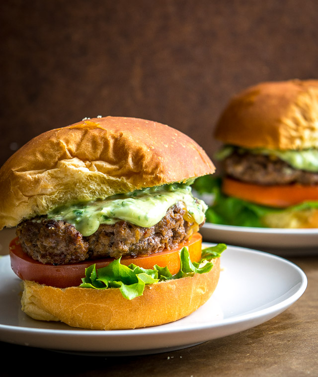 2 chipotle burgers on separate plates with creamy avocado sauce