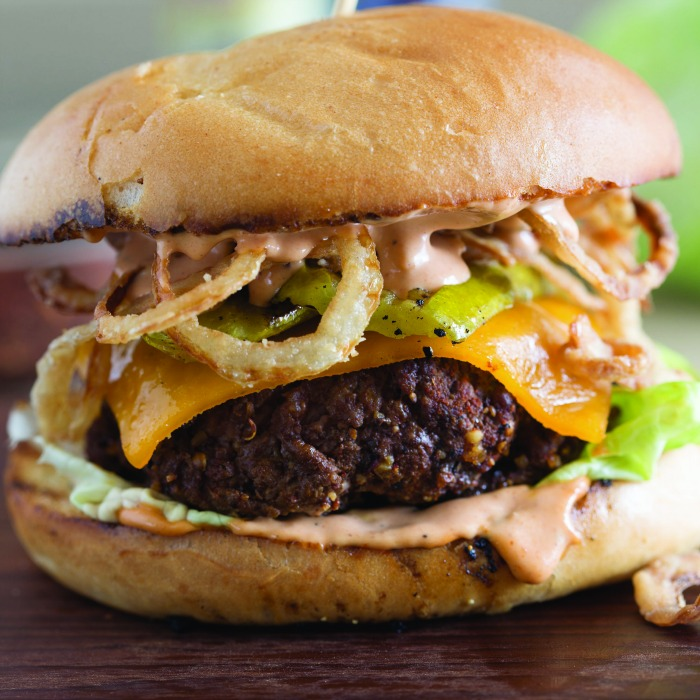 close up of cowboy burger with grilled pickles and crispy onion straws