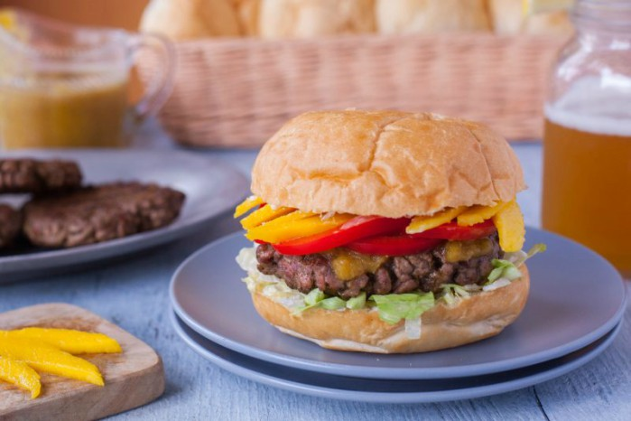 Jamaican burger with sliced mangos and extra patties and buns in the background