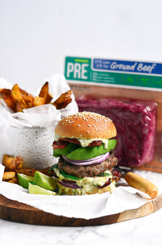 Paleo bacon garlic avocado burger on a tray with fries and ground beef in the background