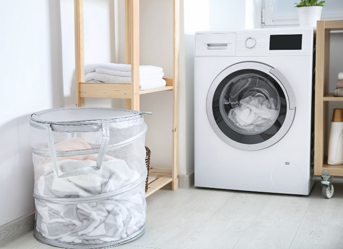 laundry room with a hamper and washing machine