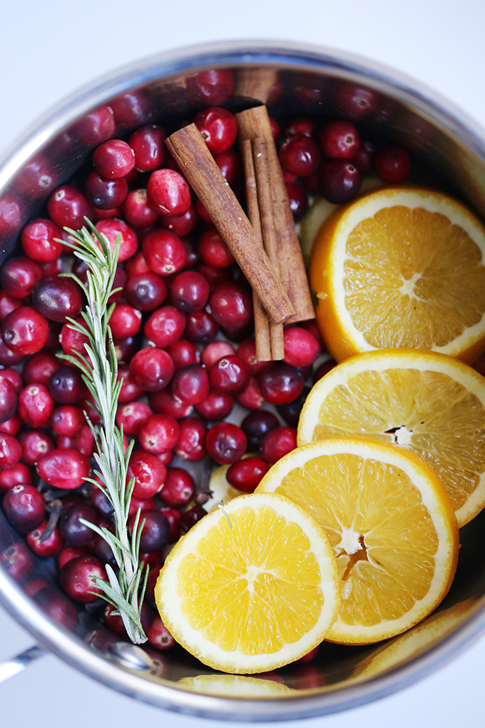 Stovetop pan filled with orange slices, rosemary, cranberries, and cinnamon sticks