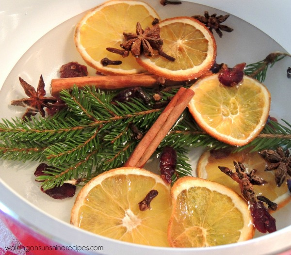 pot of water filled with orange slices, cloves, cinnamon sticks, and small evergreen branches