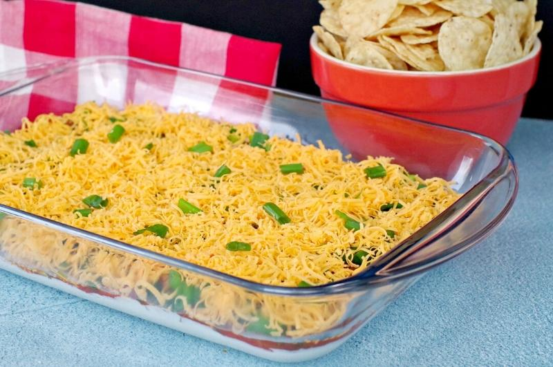 Enjoy Mexican appetizers like this easy layered nacho dip
