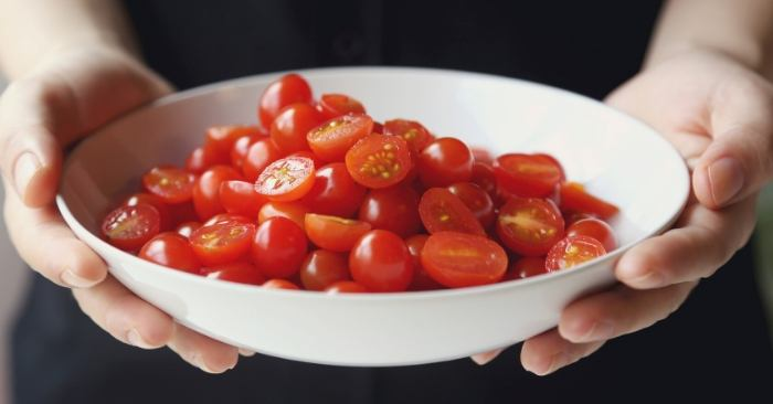 Person holding a bowl of cherry tomatoes