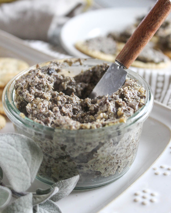 Mushroom pate with a knife in it and crackers in the background.