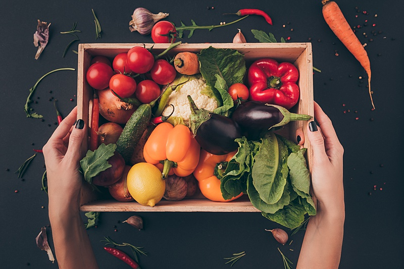 Woman holding a crate filled with foods for a plant based diets including vegetables, herbs and fruit.