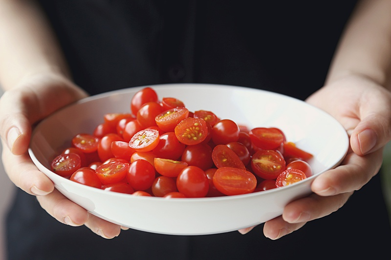 Close up of hands holding a white bowl filled with sliced cherry tomatoes.