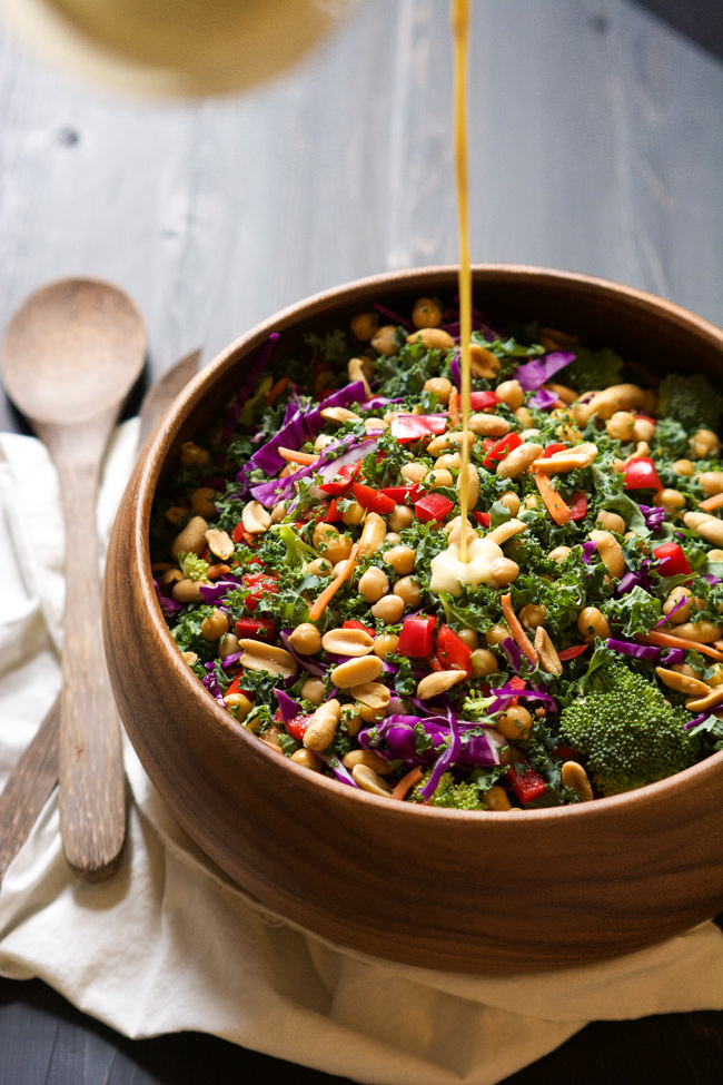 Rainbow kale salad with a fresh peanut dijon dressing being drizzled on.