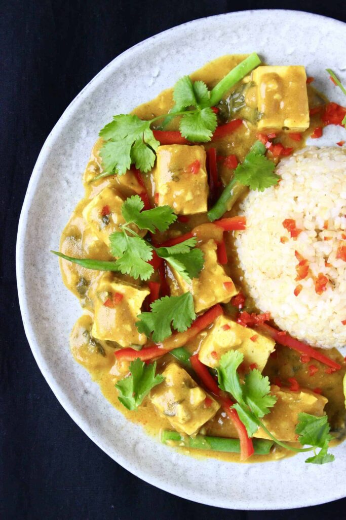 Peanut tofu satay curry on a plate with white rice.