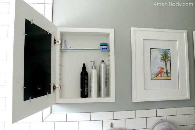 hidden storage ideas for the bathroom include built in cabinets covered by framed art