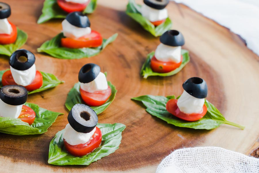Olive, mozzarella, tomato all stacked on a basil leaf