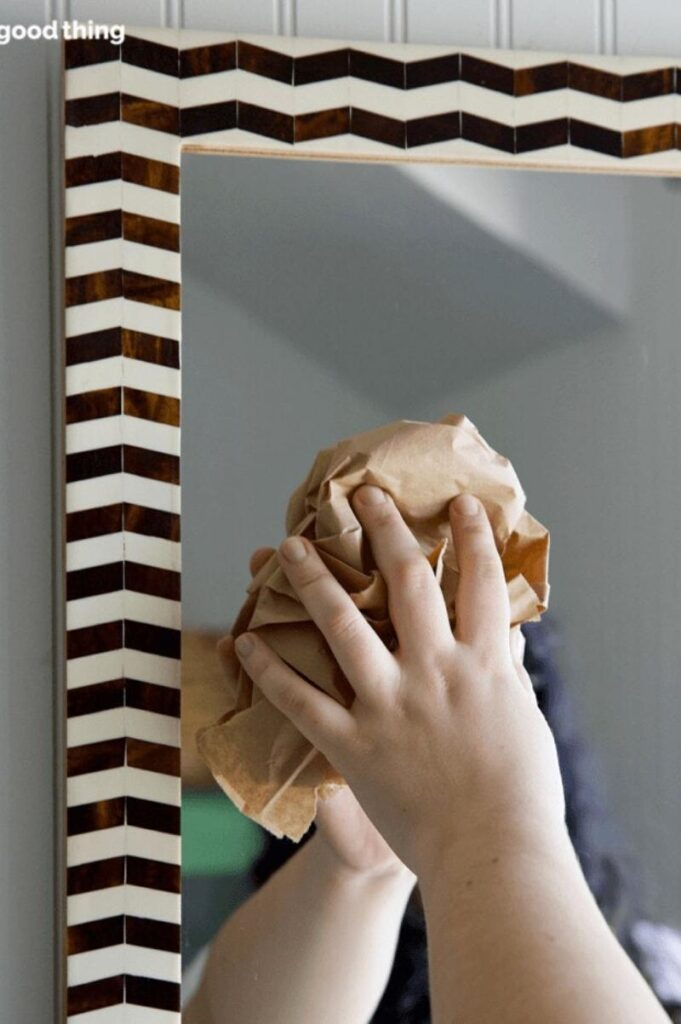 woman using a paper bags for washing mirrors