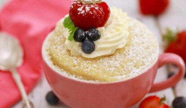 mug cake in a pink mug with cream and fruit on top
