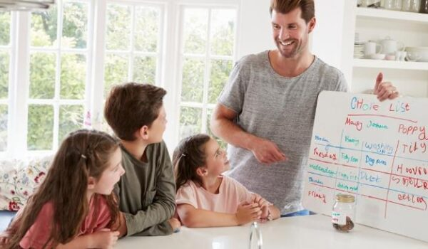 father with three kids going over a whiteboard chore chart