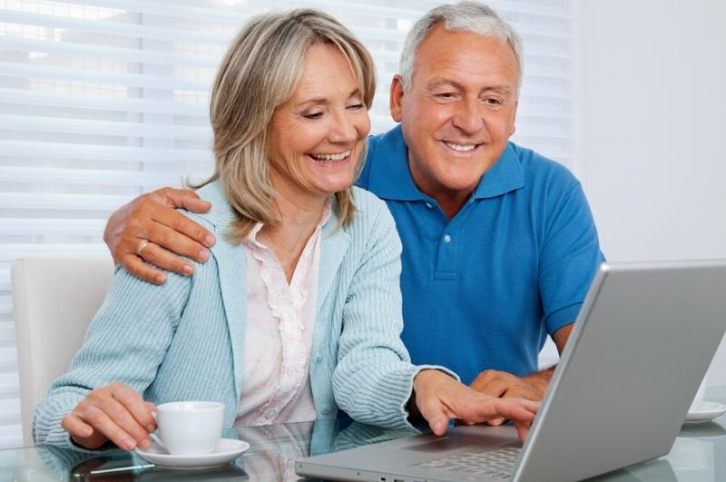 senior couple enjoying fun things to do at home on a laptop
