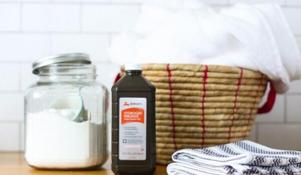hydrogen peroxide, a canister of baking soda and a basket of towels sitting on a counter