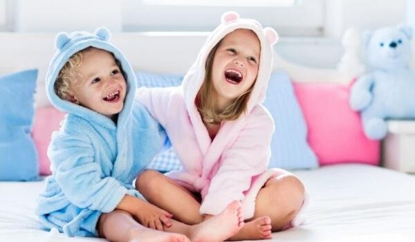 little girl and a little boy sitting and laughing while wearing hooded towels