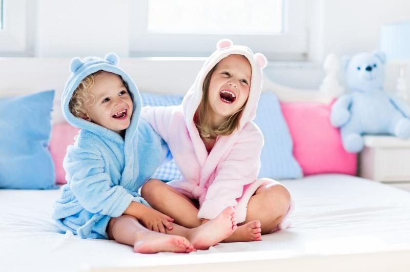little girl and little boy sitting and laughing while wearing hooded towels