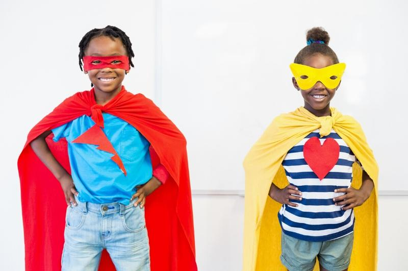 little girl and little boy standing wearing super hero capes and masks