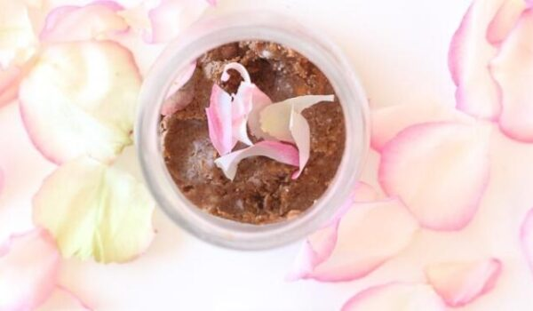 sugar scrub in a jar surrounded by rose petals