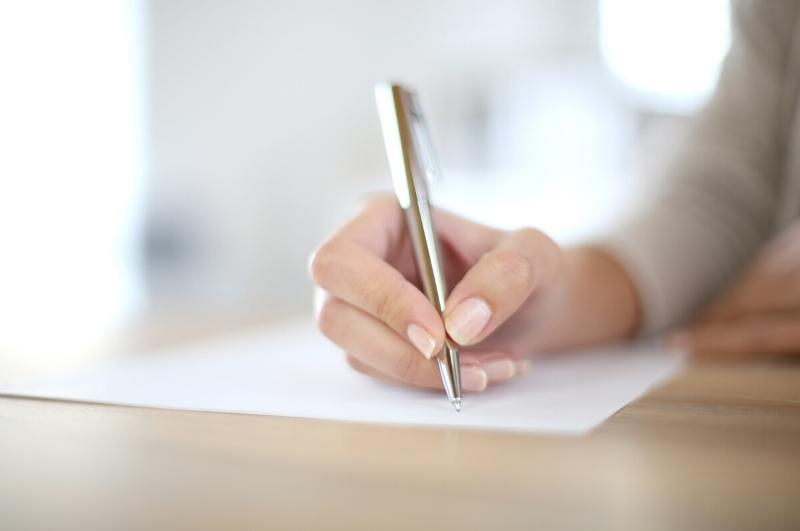 woman writing down a to do list on paper