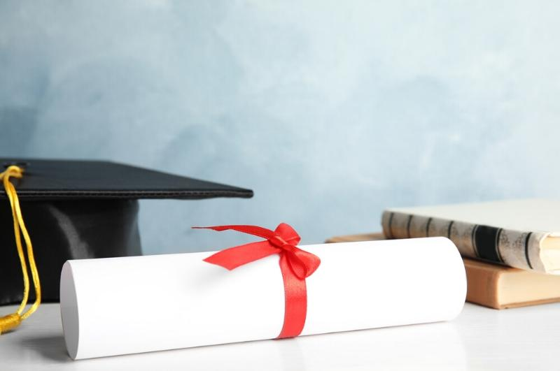 college cap, diploma and books on a table