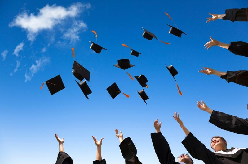 graduates throwing their caps into the air