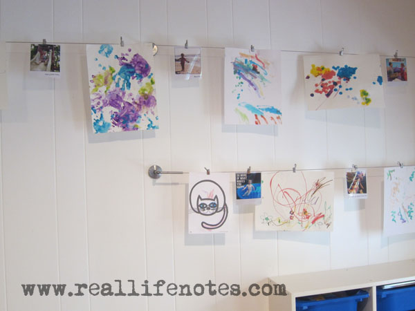 kids art displayed on a wall hanging from curtain rods