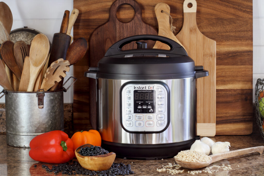 instant pot on a counter with peppers, rice and garlic