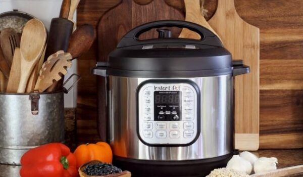 Instant Pot sitting on a counter with peppers, rice, garlic and beans