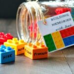 Legos with words written on them spilling out of a mason jar tipped on its side.