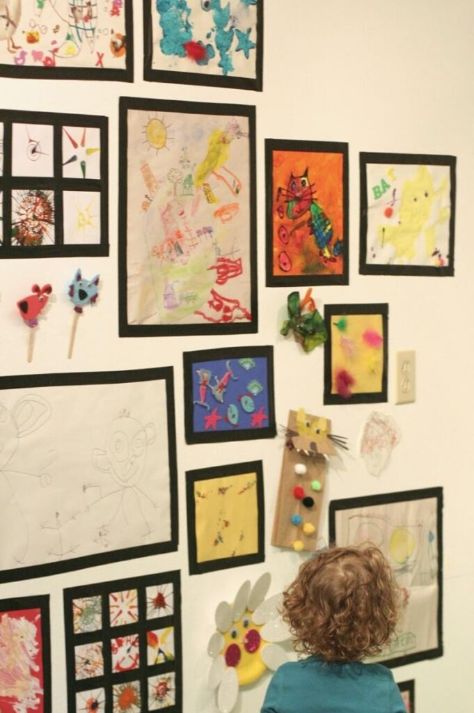 kids art displayed on a wall with tape as frame for each piece