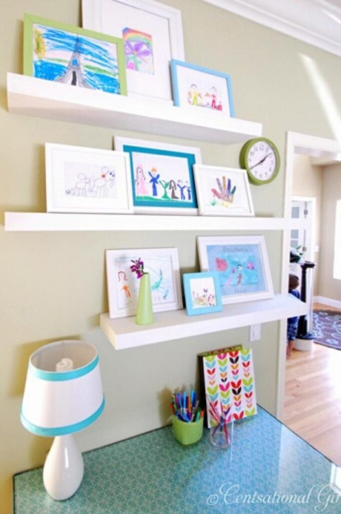 shelves holding frames with children's artwork in them