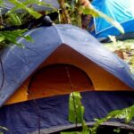 blue and orange tent set up in a summer camping area