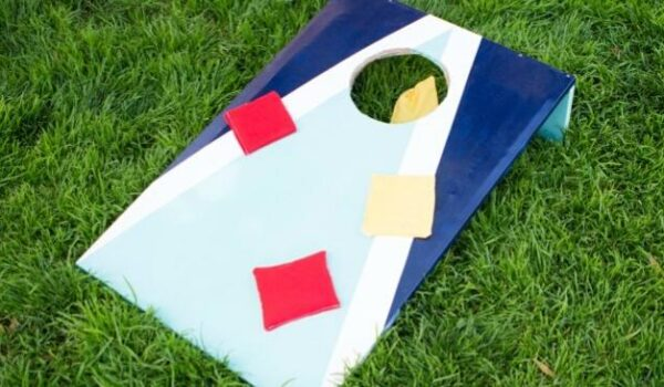 DIY cornhole board on the grass with bean bags on it