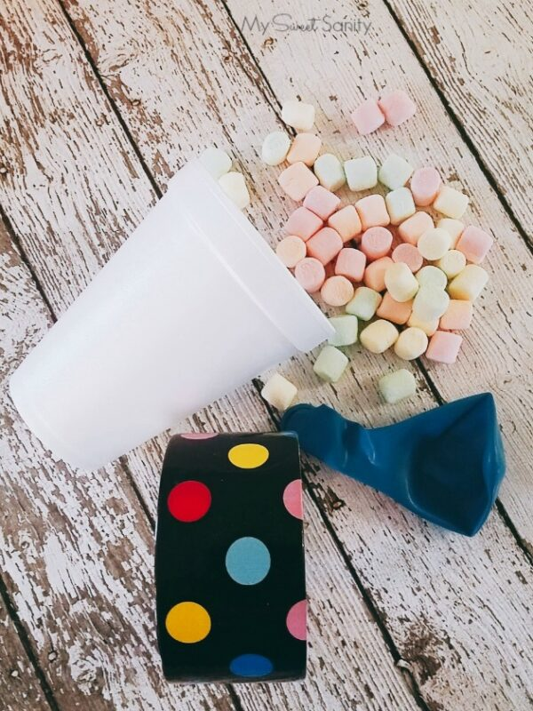 a plastic cup, washi tape, a balloon, and mini marshmallows on a table
