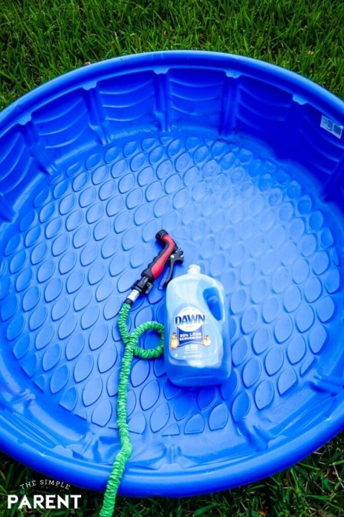 blue plastic kiddie pool with dawn soap and a hose