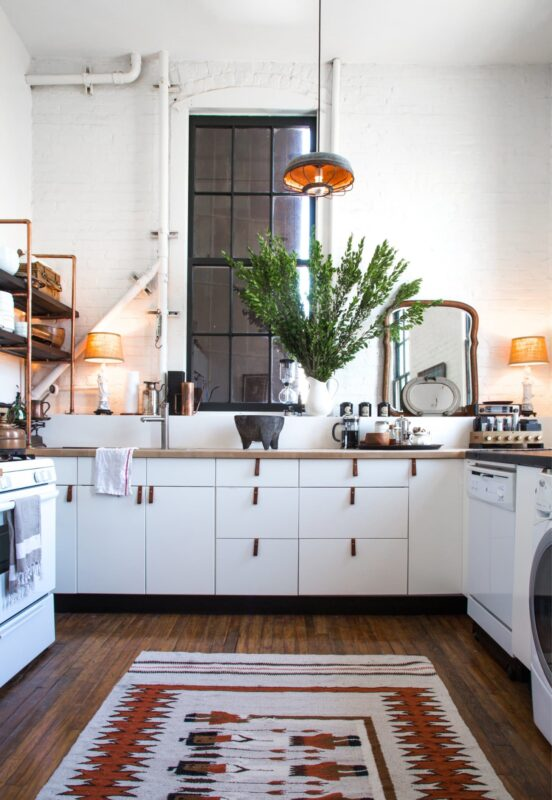 white kitchen with a rug on the floor and pulls on the cabinets