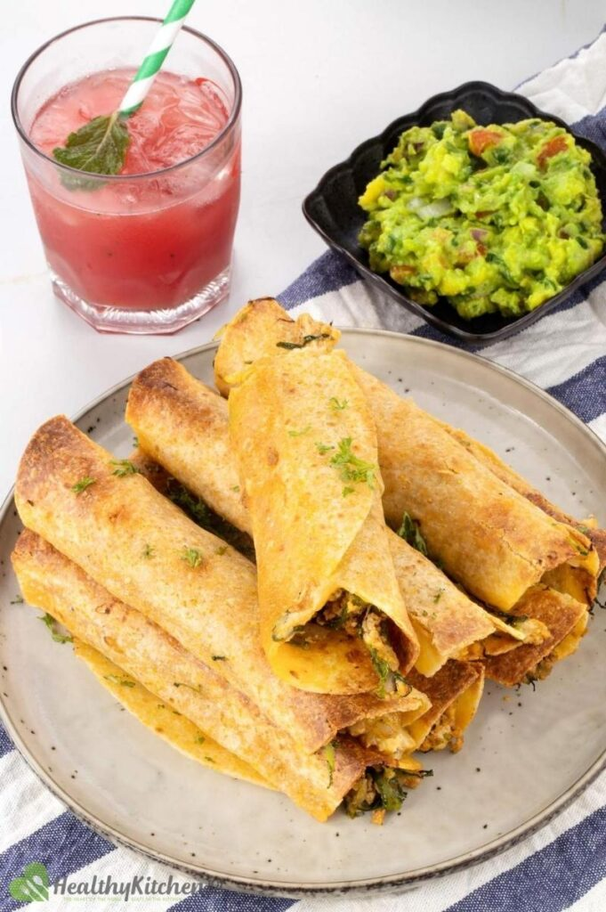 Baked chicken taquitos on a plate with a bowl of guac and a cocktail