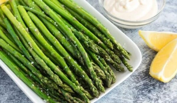 bowl of stalks of asparagus with lemon and a dish with dip