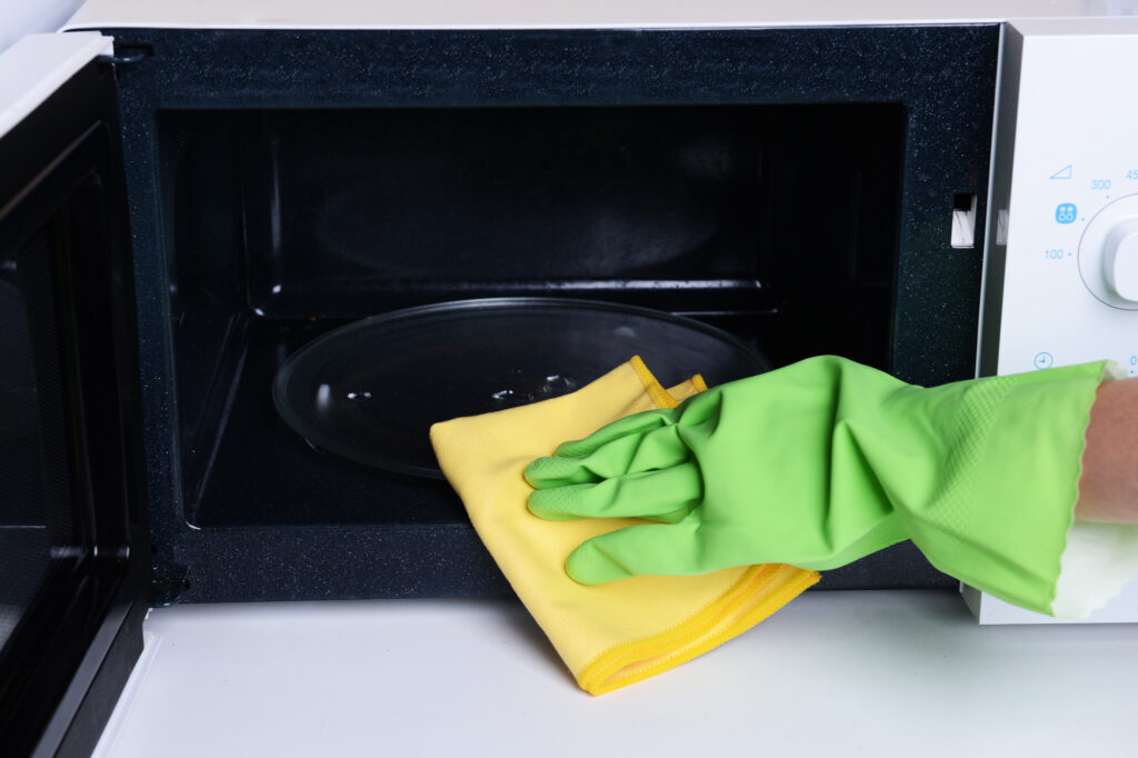 green gloved hand wiping out a microwave with a yellow rag