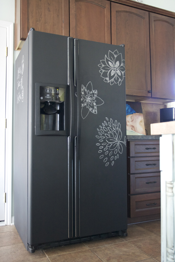 chalkboard painted refrigerator with flowers drawn on it