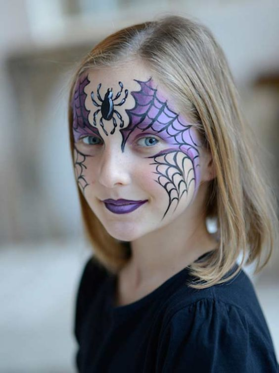 girl with black and purple spider web and spider face paint