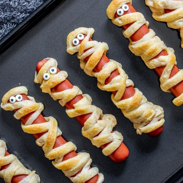 """row of """"Mummy Hotdogs"""" on a cooking tray"""